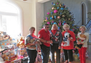 Orchid Island Members holding toys that are being donated to children in need