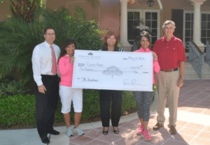 Residents of Orchid Island present a check to Camp Haven