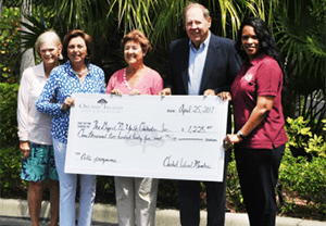 Members of Orchid Island hold check benefitting Gifford Youth Orchestra