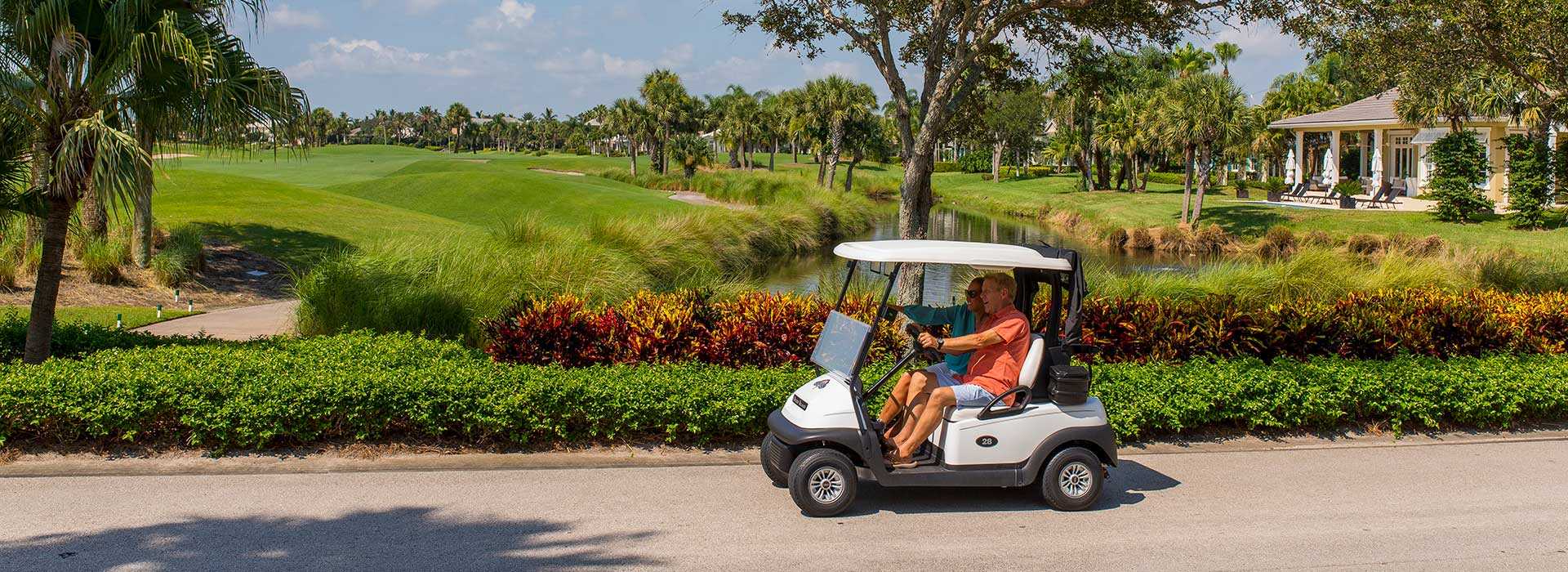 Couple riding in golf cart at Orchid Island Golf & Beach Club
